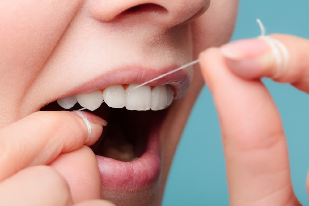 side-view-woman-face-smiling-with-dental-floss